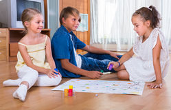 Children playing board game. Children making move on pre-marked surface of board game Royalty Free Stock Photography