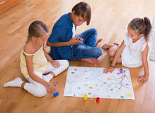 Children playing board game. Children making move on pre-marked surface of board game on the floor Royalty Free Stock Photo