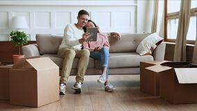 Children playing with boxes parents using tablet on moving day