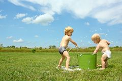 Children Playing with Bucket of Bubbles Stock Photo