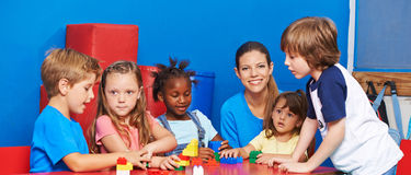 Children playing with building bricks in child care. With nursery teacher Stock Photos