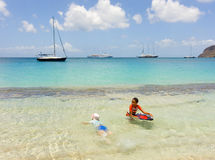 Children playing in the caribbean sea with passengers boats in the background Stock Photography