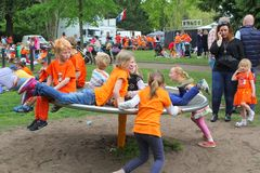 Playing children in orange clothes have fun at Kingsday (Koningsdag), Utrecht, Netherlands Stock Images