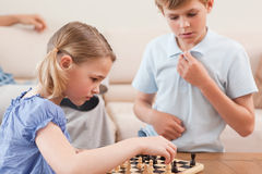 Children playing chess. In a living room Stock Images