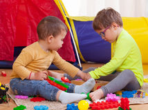 Children playing   with colored toys. Young children playing together at home Royalty Free Stock Photos