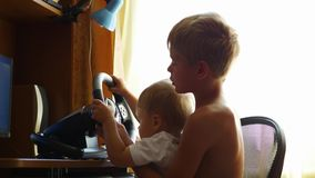 Children playing a computer game. With the wheel stock footage