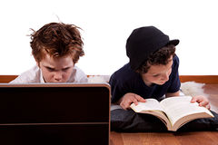 Children playing computer and reading a book Royalty Free Stock Images