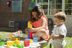 Children playing with construction toys in the garden Royalty Free Stock Photos