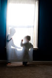 Children playing in curtain in window Royalty Free Stock Photos