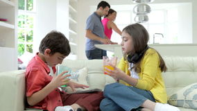Children Playing With Digital Devices As Parents Make Meal stock footage
