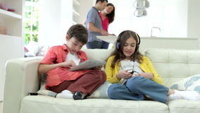 Children Playing With Digital Devices As Parents Make Meal stock video footage