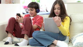 Children Playing With Digital Tablet And MP3 Player. Children sitting on sofa using digital tablet and mp3 player - sister shows something to brother. Shot on stock video footage