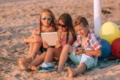 Children playing with digital tablet on sandy beach stock images
