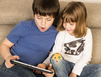 Children playing with a digital tablet. On a sofa royalty free stock photography