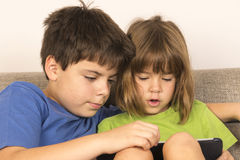 Children playing with a digital tablet Stock Images