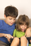 Children playing with a digital tablet Royalty Free Stock Photos