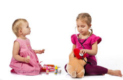 Children playing doctor with a doll Royalty Free Stock Images