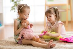 Children playing doctor with doll indoor. Children playing doctor with doll in playschool stock photos