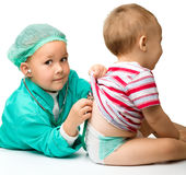 Children are playing doctor with stethoscope. Cute children are playing doctor with stethoscope, isolated over white Royalty Free Stock Photography