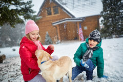 Children playing with dog on snow in winter holiday Stock Photo
