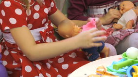 Children playing with dolls in kindergarten. Close up stock footage