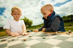 Children playing draughts or checkers board game outdoor Royalty Free Stock Images