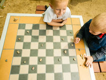 Children playing draughts or checkers board game outdoor. Draughts board game. Little boys clever children kids playing checkers thinking, outdoor in the park royalty free stock image