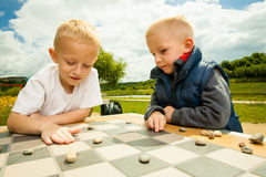 Children playing draughts or checkers board game outdoor. Draughts board game. Little boys clever children kids playing checkers thinking, outdoor in the park royalty free stock images