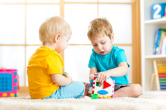 Children playing with educational toys, arranging and sorting colors and forms. Learning through experience conception. Stock Photography