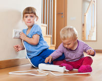 Children playing with electrical extension and outlet. At home stock photo