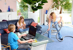 Children playing electronic games and mother doing homework Royalty Free Stock Photography