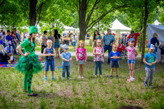 Children playing with entertainer. Zaporizhia/Ukraine- May 28, 2017: Charity Family festival – children playing with entertainer – smiling young woman in a Royalty Free Stock Photography