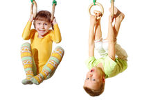 Children playing and exercising on gymnastic rings stock image
