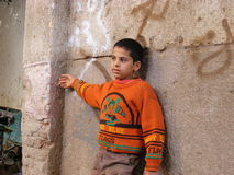 African boy child in the door village in an orange sweater posed against a stone background Royalty Free Stock Photography