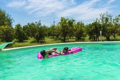 Children playing with a float in an outdoor pool. Children playing with a water mat or a float in an outdoor pool between fields of crops in Sicily, Italy stock photo
