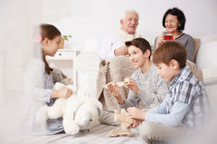 Children playing on a floor. And their grandparents sitting on a sofa Stock Photography