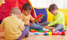 Children playing on  floor. Two girls and boy with toys on  floor at home Royalty Free Stock Photography