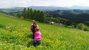 Children playing on a flowering lawn against the backdrop of the Carpathian Mountains stock video footage