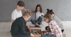 Children playing foosball at home. Group of boys and girls playing foosball at home stock video