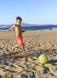 Children playing football on the beach.  Royalty Free Stock Image