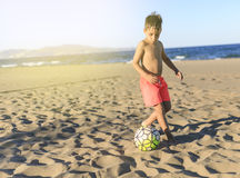 Children playing football on the beach.  Stock Photos