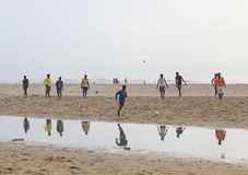 Children playing football in the beach, India. We can see children playing football in the beach Stock Photo