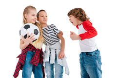 Children playing football. Boy screaming on girls with soccer ball isolated on white, children sport concept stock photography
