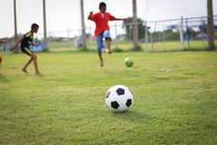 Children playing football on the field Stock Photos