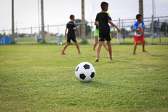 Children playing football on the field Stock Image