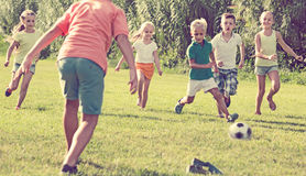 Children playing football on meadow Stock Photography