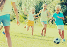 Children playing football on meadow Stock Photos