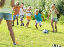 Children playing football on meadow. Happy cheerful  children playing football on meadow outdoors . Selective focus Royalty Free Stock Photos