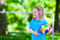Children playing football outdoors Stock Images