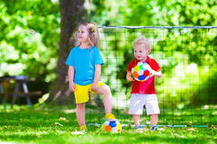 Children playing football outdoors. Two happy children playing European football outdoors in school yard. Kids play soccer. Active sport for preschool child stock photography